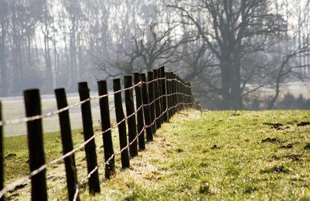 A farm fence on a farm in the winter sun. Stock Photo