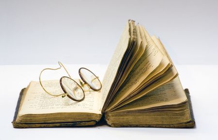 A old open book with a pair of antique glasses on it.
