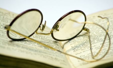 A close-up of a old open book with a pair of antique glasses on it.