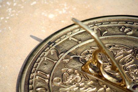 sun dial: A brass sun dial at 12h26.