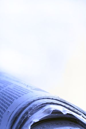 A part of a news paper with a blue liget on it and a white background.