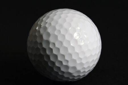 A golf ball isolated on a black background. Standard-Bild