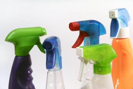 Five cleaning spray bottles isolated on a white background.