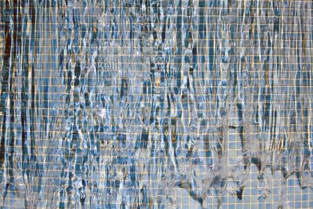 that: Water that is flowing over a mosaic wall.
