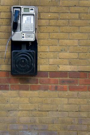 A public telephone against a brick wall.