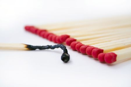 burned out: A row of red head matches with one burned out. Stock Photo