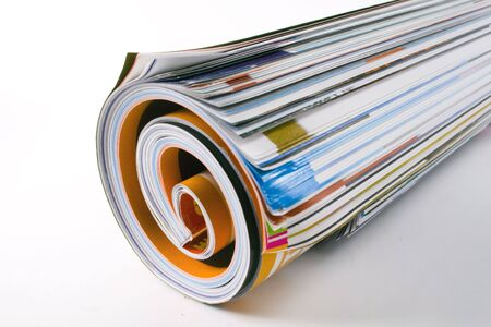A close-up of a rolled magazine on a white background. Stock Photo