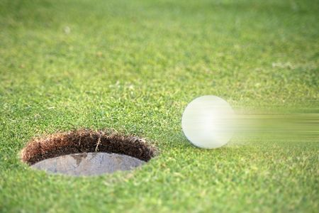 A golf ball on a golfing green next to a hole illustrating movement.