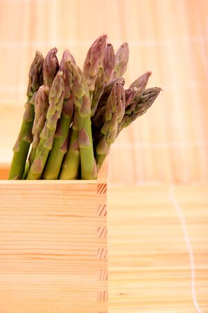 fibber: A bunch of fresh asparagus in a wooden box at the market.  Stock Photo