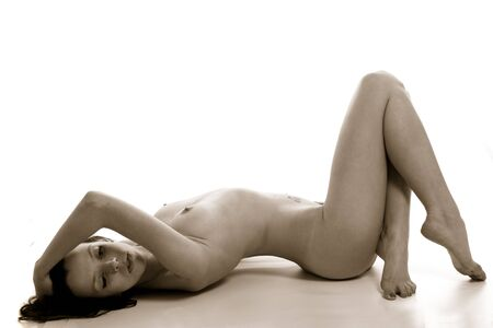 Black and white image of a nude woman on a black background.