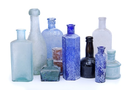Old antique glass bottles in different colours on a white background.  Stock Photo