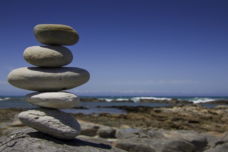 A pile of five big grey pebbles on a rock in front of blue sky background with the coast line in the background.