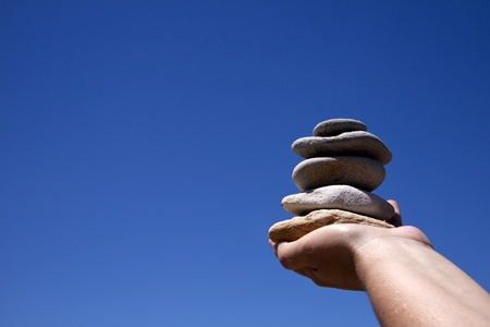 Five Zen stones in a woman hand holding it up to the blue sky.