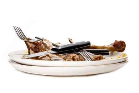 wash dishes: Una pila de placas sucios con huesos.
