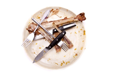 A stack of dirty plates with bones.