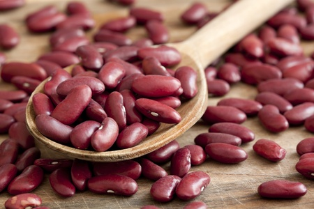 Dried red beans on a wooden spoon with a shallow depth of field.  Standard-Bild