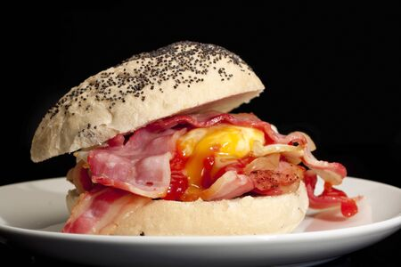 Bacon and egg roll with tomato sauce with a black background.