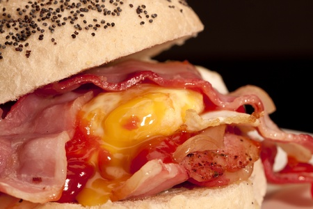 A close-up photograph of a Bacon and egg roll with tomato sauce with a black background.  photo