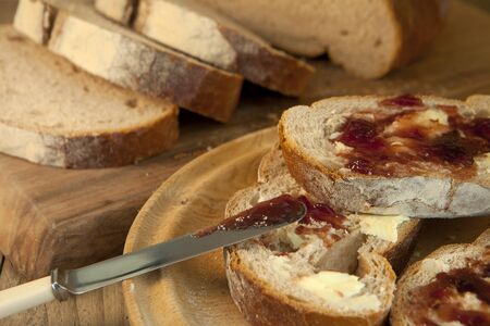 fibber: Freshly baked bread with butter and delicious raspberry jam. Stock Photo
