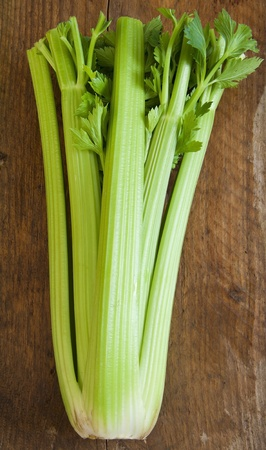 A bunch of celery on a wooden board.