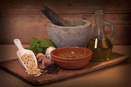 A moody photograph of all the ingredients to make Italian home made pesto in a rustic way.  photo
