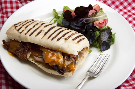 Home made panini with roasted turkey and a small green salad to the side.  photo