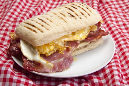 Home made panini with egg and bacon on a small white plate, ready to be eaten.