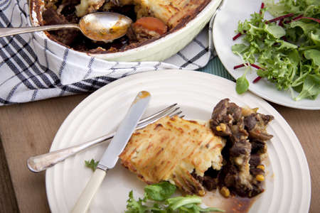 A delicious home made meat pie on a wooden table that makes your mouth water.  photo