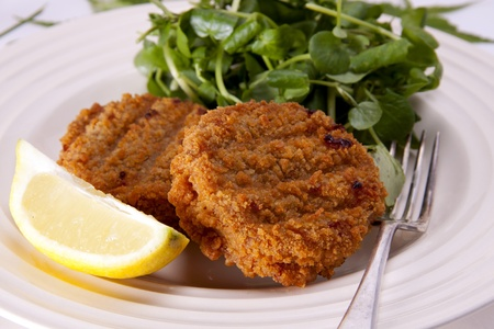 Two homemade fishcakes with a slice of lemon and a small watercress salad.