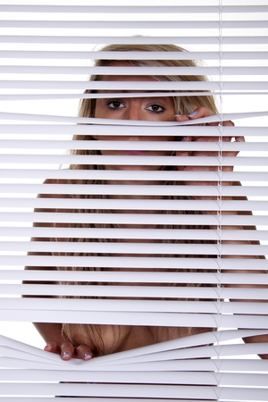 A young blond woman looking trough venison blinds. Stock Photo - 10267851