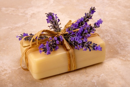 A bar of handmade lavender soap decorated with fresh lavender.