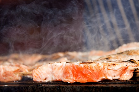 Fresh salmon being cooked on an outdoor barbeque for an alfresco meal.  photo