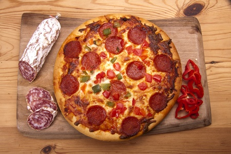 Home made Italian pizza with salami and peppers on a wooden board.  photo