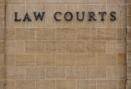 Law courts sign on an old stone wall with copy space.