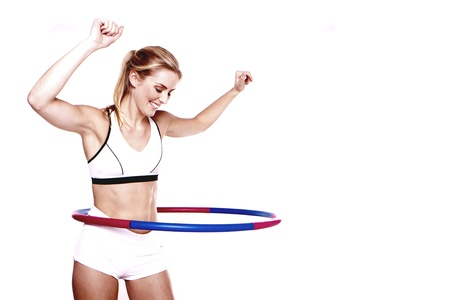 hula girl: A young blond woman doing exercise with a hula-hoop. Stock Photo