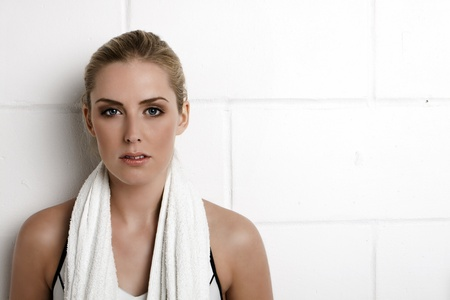 Beautiful blond woman standing against a wall in a gym with a towel around her neck.  Stock Photo