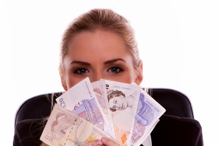 Young businesswoman holding ten and twenty pound notes in her hand. Standard-Bild