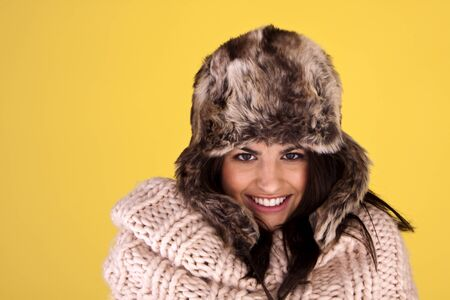 A portrait of an attractive woman wearing a fur hat to keep warm for winter.  photo