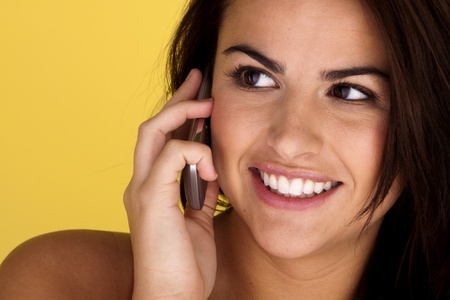 A cheerful and happy young woman is talking on her mobile cell phone.  Stock Photo