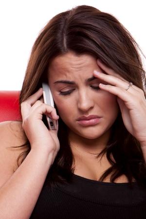 femme inqui�te: Une jeune femme est triste car elle est de parler au t�l�phone cellulaire ici mobile. Banque d'images