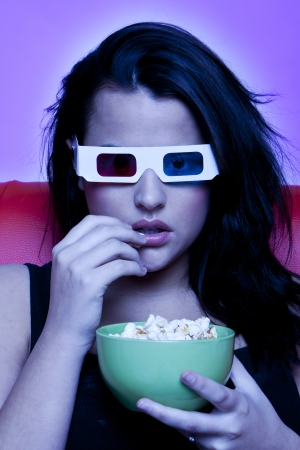 A woman is sitting on a red sofa watching a movie in 3D and eating popcorn.
