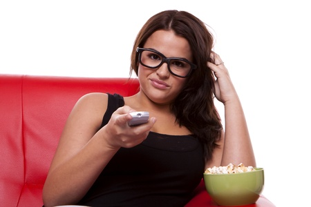 A young bored woman is sitting on a sofa flicking trough TV channels and eating popcorn.