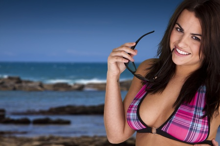 A beautiful woman wearing a bikini top holding sunglasses standing near the ocean.  photo