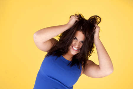 An attractive woman being happy with herself in playfully pulling her hair. photo