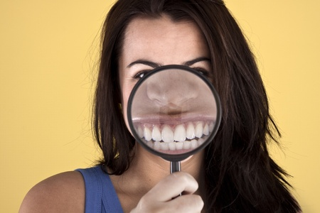 showoff: Woman holding a magnifying glass in front of her face to show-off her clean teeth.  Stock Photo