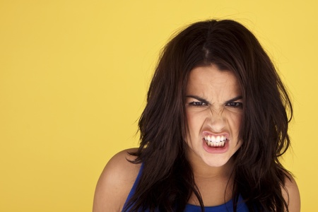 Headshot of a young and angry woman on a yellow background.