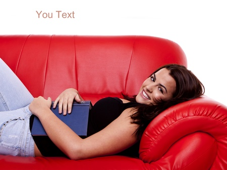 A young beautiful woman relaxing on a red sofa with a book on her front.  Stock Photo