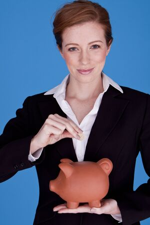 Young attractive businesswoman holding a piggybank and pound coins on a blue background  photo