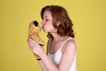 Beautiful young woman holding and kissing her small toy bear  photo