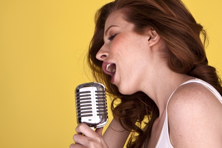 Retro redhead female singer with microphone singing her heart out Stock Photo - 12411407
